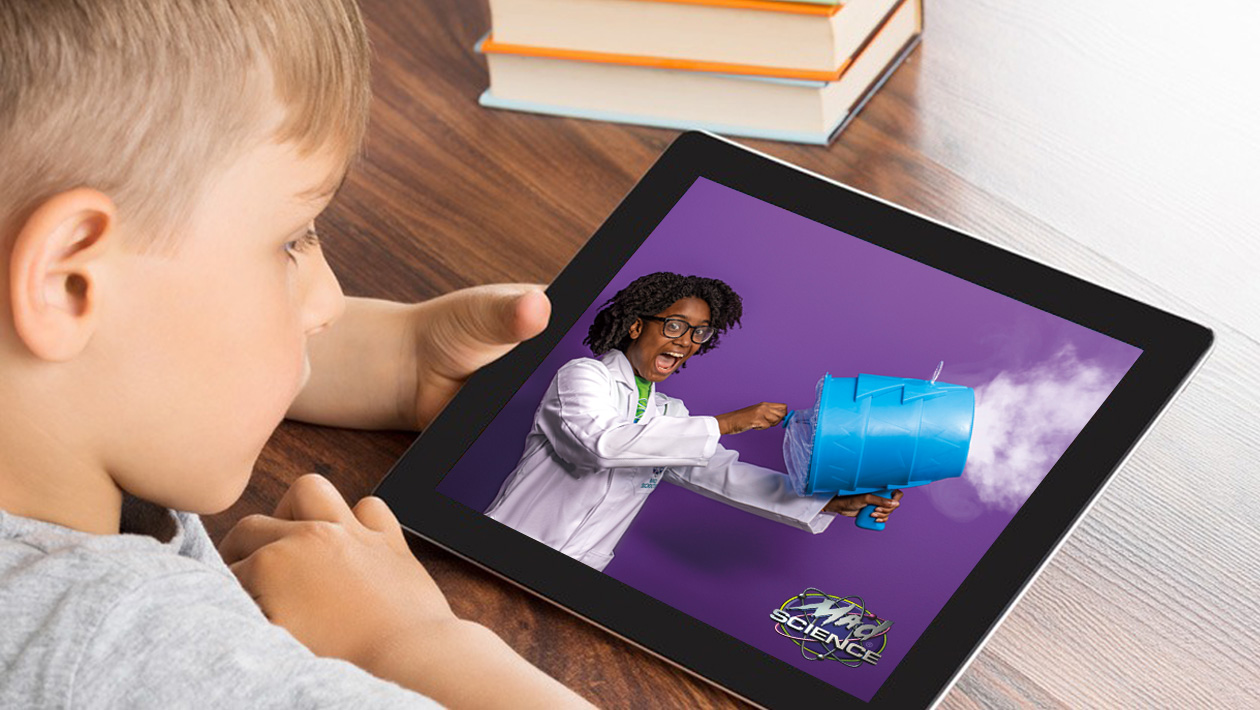 Boy looking at ipad with a mad scientist on the screen blowing smoke out of a smoke machine