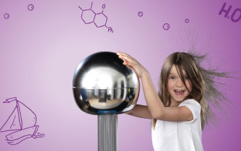 Girl in white shirt coat touching electric silver ball causing her hair to go up.