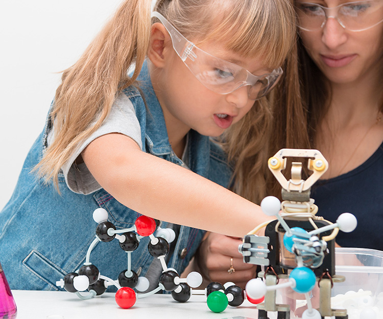A woman teacher and girl collect molecules and conduct experiments. On the table are a robot and beakers with liquid inside.
